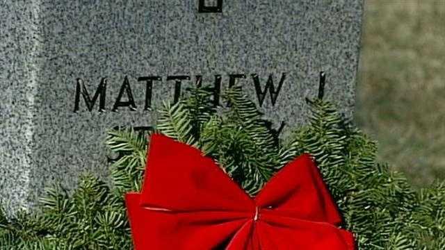 Volunteers place wreaths to honor fallen soldiers