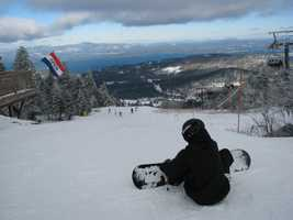A snowboarder gears up for a run from the top of Gunstock in Gilford, Friday where about 15 inches of snow was recorded at the summit. The view to the East includes a still-open Lake Winnipesaukee and the Ossipee Range. Gunstock, like many other resorts across the East, was slammed with business, Friday after the well-timed Nor'easter left over a foot of new snow.