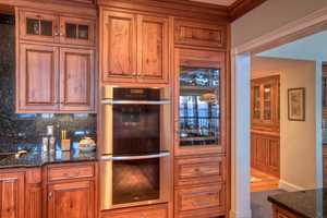 Appliances include a Viking Refrigerator, a warming drawer and a Subzero wine refrigerator with  2 beverage drawers and cherry panels that match the rest of the kitchen's cabinets and paneled appliances.