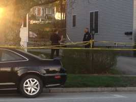Two police officers are standing in front of the home, and others have been moving in and out.