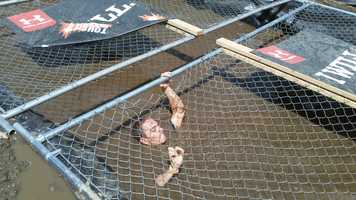 "WMUR Assignment Editor Trent Spiner uses upper body strength to work his way through ""Cage Crawl"" -- a muddy pit of water covered by chain-link fences."