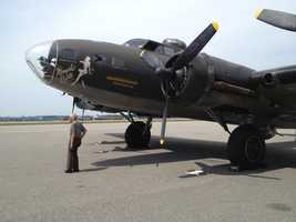 Former World War II pilot Al Kramer stands with the restored bomber.