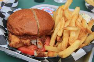 Freshly battered and fried fish sandwich with fries.