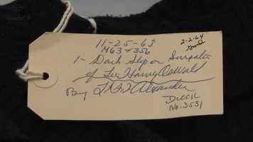 "The evidence tag reads ""Dark slip on sweater of Lee Harvey Oswald."""