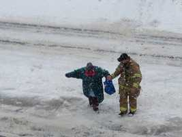 Heavy snow throughout the day made the trip difficult, so he got out of the apparatus to help her across the street.