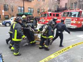 Firefighters working on fellow firefighter brought out of burning building on Beacon Street