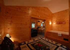 The master bedroom, in addition to having this magnificent hot tub, has a queen-sized bed.