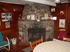 The lodge has a rustic stone fireplace and knotty pine interior and antique furnishings.