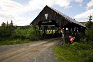 """Happy Corner Bridge in Pittsburg, N.H.Constructed in the 1800s. One theory as to how the bridge got its name is that an elderly man lived in a house on the northeast corner and he often played music and danced. People would congregate at his house and have a """"happy"""" time."""