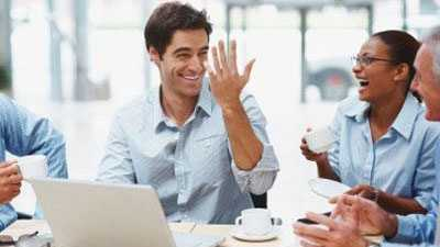 Office workers laughing in meeting