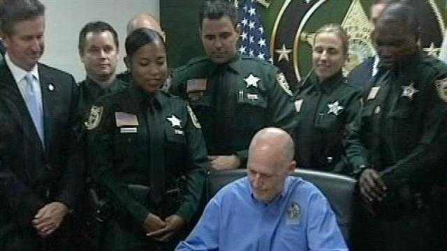 Gov. Rick Scott signs a ceremonial auto insurance reform law at the Palm Beach County Sheriff's Office.