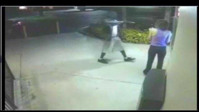 Surveillance video shows a gunman wearing a leather jacket rob a woman at a Pompano Beach ATM.