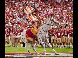 The tradition of Chief Osceola planting a burning spear at midfield while riding his Appaloosa horse, Renegade, before every Florida State home game began in 1978. (Photo: Ross Obley/FSU Sports Information)