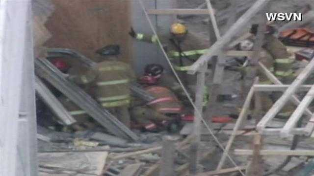 Firefighters try to rescue some workers trapped in the rubble of a parking garage that collapsed at the western campus of Miami Dade College.