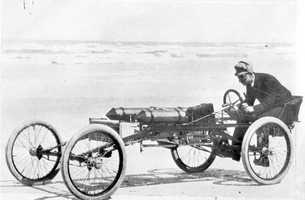 Visitors at Ormond hotel discussed the idea of an auto race on the beach. Alexander Winton had already built and driven a race car called the Bullet while Ranson E. Olds was manufacturing small two-seaters and had sold a sightseeing bus in Ormond. Winton agreed to bring his car down and Olds said that he would build a suitable challenger. The two cars met and had identical speeds of 57 mph. It was fine sport and neither claimed victory.  This photo was taken in 1897.