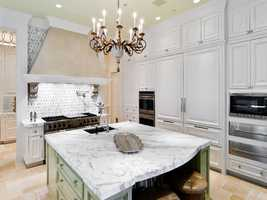 This marble topped island really catches your eye in this beautiful kitchen.