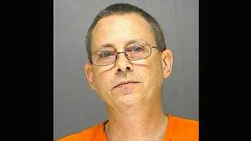 Police say Richard Watson held his wife's head face down in their dog's water bowl after an argument over frozen pizza.