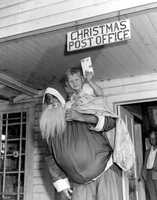 1947: Young Lewis Yates rides in Santa's sack at the Christmas, Florida post office.