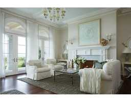 Formal sitting area feels light and airy thanks to the large french doors and the light-blue accents.