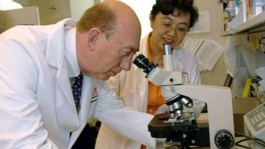 Generic Doctor Looking At Microscope