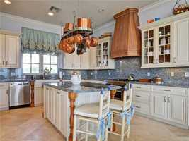 Modern kitchen complete with a spacious island and hanging pot rack.
