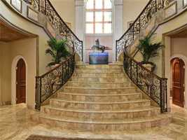 The main entry foyer opens to a rotunda foyer with a dramatic twin marble staircase which leads to the primary bedrooms.