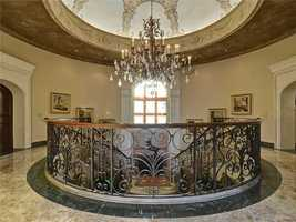 The top of the flamboyant staircase features a beautifully painted dome and chandelier.