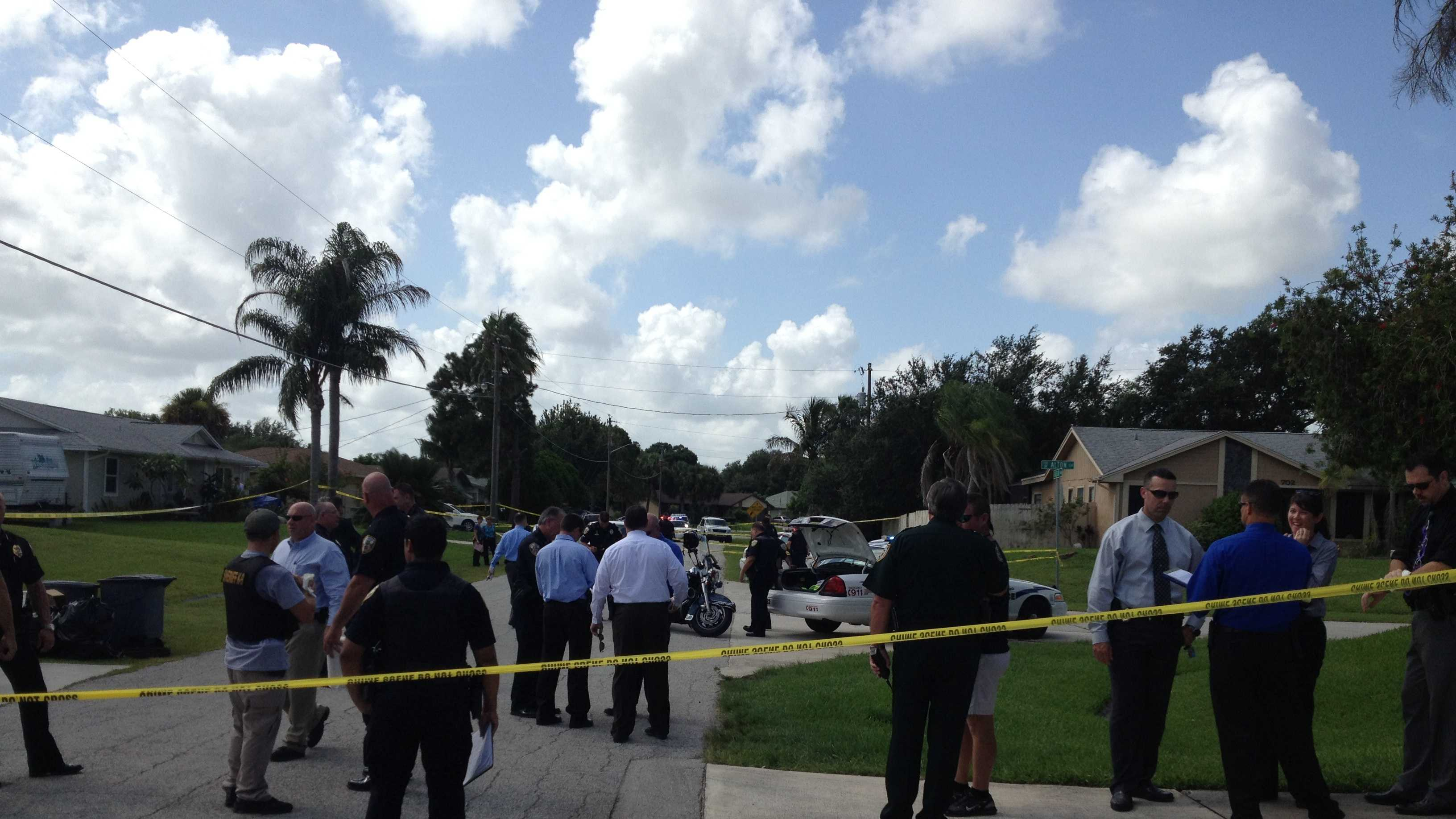 Police gather at the scene in Port St. Lucie where a shootout took place after one of three bank robberies.