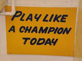 "The slogan ""Play Like a Champion Today"" is hand-painted in blue letters on a sign located in a stairwell between the home team locker room and the tunnel to the field of Notre Dame Stadium. It is a tradition for Notre Dame players to touch it on their way out of the locker room."