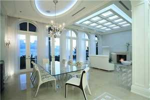 Designed by The Benedict Group and crafted by Seadar Builders, this lavish four-level residence makes a statement of clean-lined modern glamor in the artfully styled interiors as seen in this magnificent dining room.