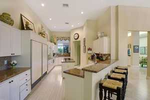 Custom cabinetry, a granite topped island, and breakfast bar are featured in this kitchen.