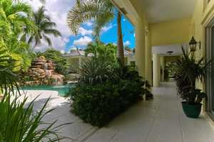 Lush landscaping surrounds the pool area.