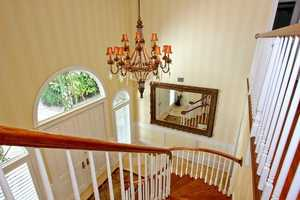 The foyer boasts a chandelier and winding stairwell.