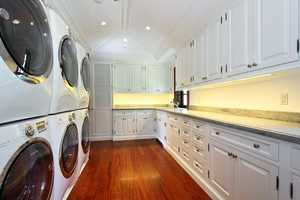 Three washers and three dryers in this large laundry room.