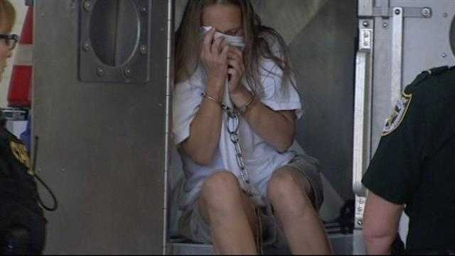 Georgia Scordamaglia covers her face as she led into the St. Lucie County Jail.