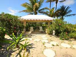 A shaded cabana is nestled in the dunes, a short walk from the beach.