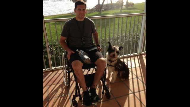 Derek Herrera poses with his service dog, Shaggy.