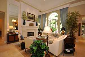 Stunning living room with stone fireplace, decorator touches and quality window treatments.