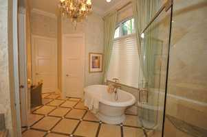 A free-standing tub in this classy master bathroom.