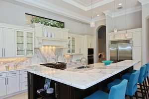 A pop of blue in the kitchen looks breathtaking among the marble counter tops and stainless steel appliances.