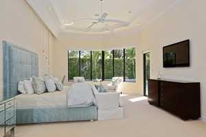 Master bedroom features vaulted ceilings and creatively placed recessed lighting.