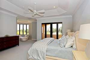 Master bedroom features a private balcony and quaint sitting area.