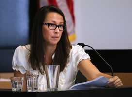 With glasses from The Players Club sitting in front of her, and holding a copy of her deposition from the civil case, Cathleen Lewter testifies on the fifth day of John Goodman's retrial Thursday, October 16, 2014. Goodman is charged with DUI manslaughter in the death of Scott Wilson. (Lannis Waters / The Palm Beach Post)