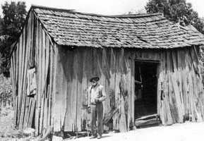 Former slave, George Carson, standing by the house in which he lived after coming to Florida in 1875.
