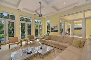 The living room offers panoramic outdoor views and is lit masterfully.