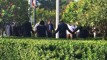 The Jones' family and rally organizers praying outside the Palm Beach County Courthouse before the news conference and rally began.