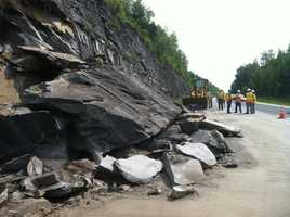 Crews look at the mess a rockslide left near Exit 6 in Williamstown.