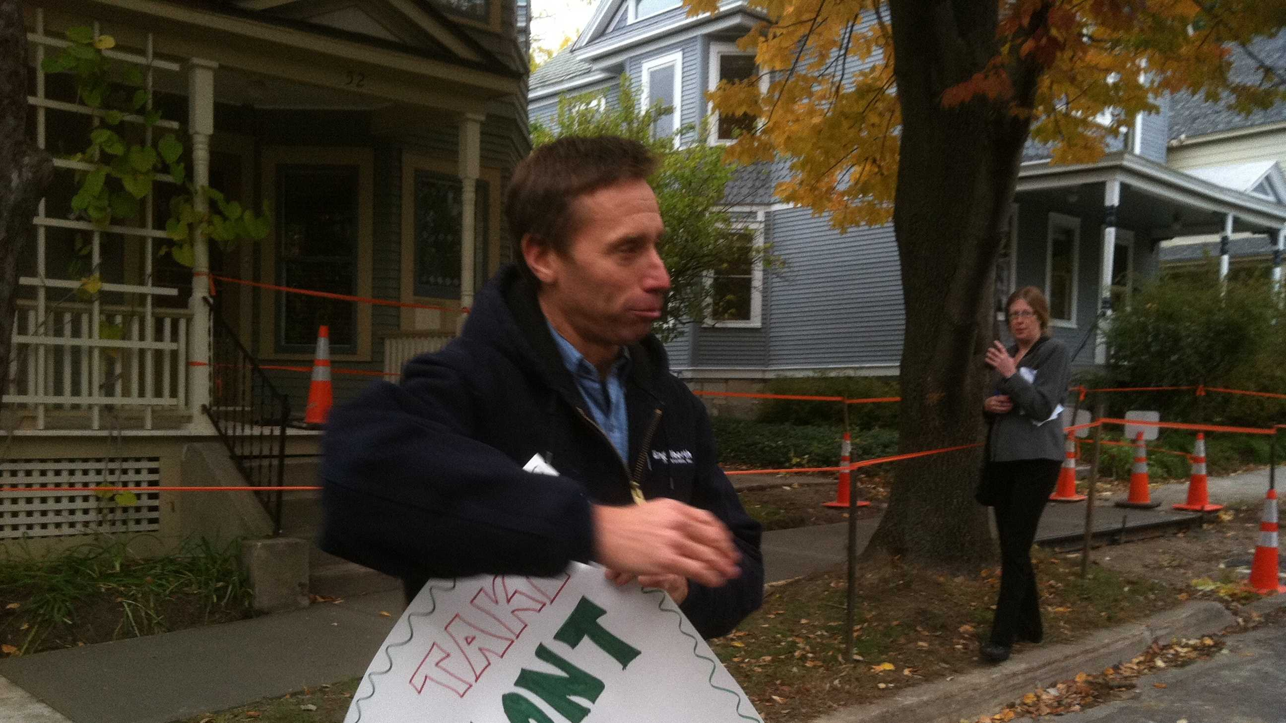 Health care reform activist Peter Sterling holds a sign in front of the home of 'Vermonters First' benefactor Lenore Broughton in Burlington.