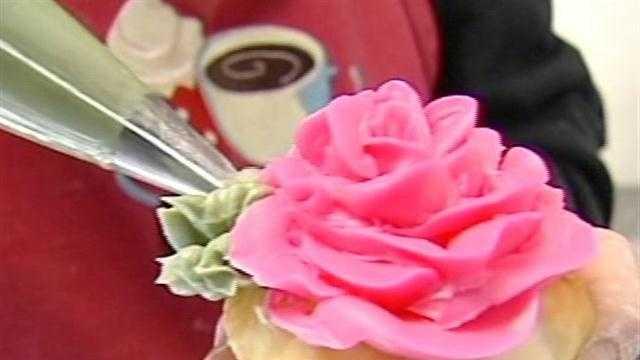 Gretel-Ann Fischer, owner of Cupp's Bakery in Winooski, decorates a cupcake.