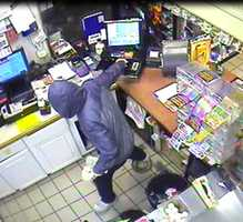 The suspect is seen with his hand in the cash register.
